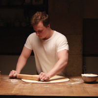 "Tim Kalkhof as Thomas prepares dough in a scene from ""The Cakemaker."""