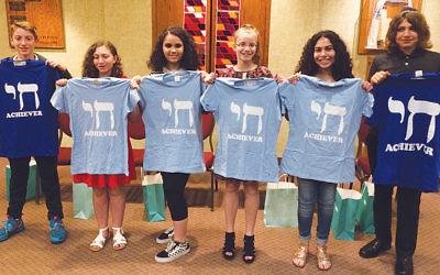 Brad Leopold, Sherry Hausman, Jessica Rosenblum, Emily Skobac, Gabrielle Brayman, and Jon Mousserie display their graduation T-shirts from the religious school at the JCC of Paramus/Congregation Beth Tikvah.