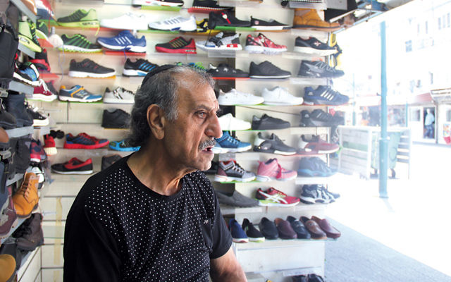 Eli Shirazi, who has owned a shoe store on Neve Shaanan Street for 45 years, bemoans the decline in foot traffic. He says Israelis are afraid to come to the neighborhood. (Photos by Ben Sales)