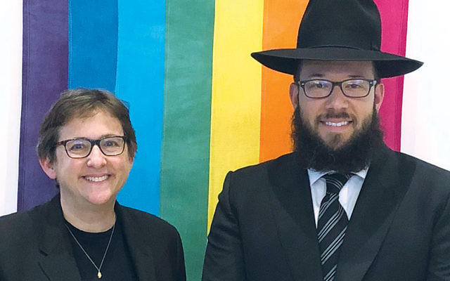 Congregation Beit Simchat Torah's senior rabbi, Sharon Kleinbaum, and Rabbi Mike Moskowitz stand in front of a rainbow flag. (Courtesy of CBST)