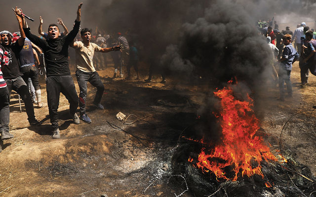 Palestinians protest at the border fence with Israel in Gaza City on May 14, 2018. (Spencer Platt/Getty Image)