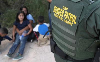 Central American asylum seekers wait as U.S. Border Patrol agents take them into custody near McAllen, Texas, June 12, 2018. (John Moore/Getty Images)