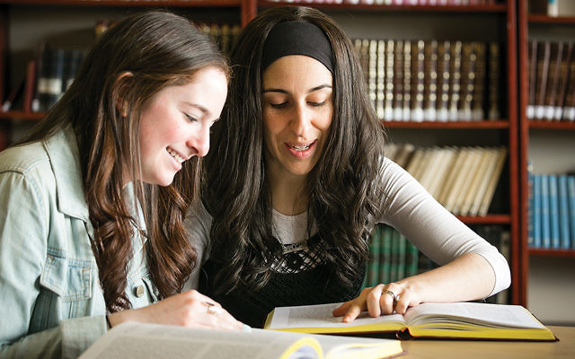 Rena Levin of Teaneck, left, and Shoshana Charnoff, an educator from the OU's JLIC program, work together at a women's learning event at Queens College. (Courtesy OU)