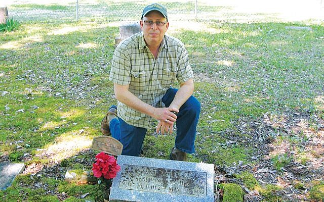 Documentarian Stephen Fischler of Teaneck kneels at the headstone of Professor Ernst Borinski, buried on the campus of Tougaloo University in Mississippi.