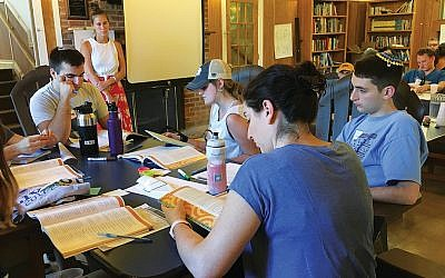 Counselors at Camp Ramah study guidebooks on Youth Mental Health First Aid Training.