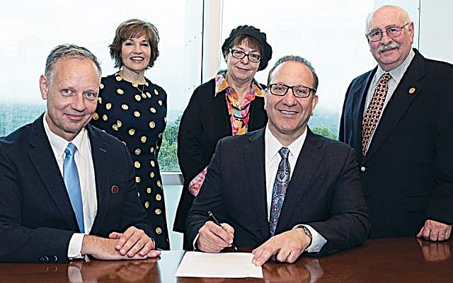 Ramapo provost Stefan Becker and Touro College of Pharmacy dean Henry Cohen sign the agreement creating a fast-track pharmacy degree program. Top, from left: the school's assistant dean for admissions and enrollment management, Heidi Fuchs, is joined by Rena Bacon, Ph.D., a biology professor at Ramapo, and Edward Saiff, Ph.D., the dean of Ramapo's School of Theoretical and Applied Science. (Courtesy Touro)