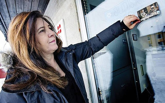 Carinne Sjoberg peels off a sticker that neo-Nazis left on the door of what used to be the Jewish community center of Umea, Sweden. (Courtesy of Sjoberg)