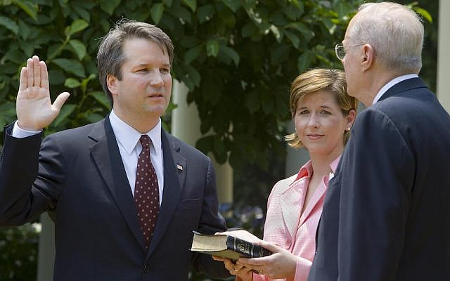 Washington, UNITED STATES:  Brett Kavanaugh (L) is sworn in as a US Court of Appeals Judge for the District of Columbia by US Supreme Court Justice Anthony Kennedy (R) as Kavanaugh's wife Ashley (C) holds the Bible during ceremonies 01 June 2006 in the Rose Garden of the White House in Washington, DC.       AFP Photo/Paul J. Richards  (Photo credit should read PAUL J. RICHARDS/AFP/Getty Images)