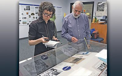 Dyani Feige of Philadelphia's Conservation Center for Art and Historic Artifacts examines a display at the Jewish Historical Society of North Jersey, accompanied by Marty Feitlowitz, the society's vice president. (Jewish Historical Society of North Jersey)