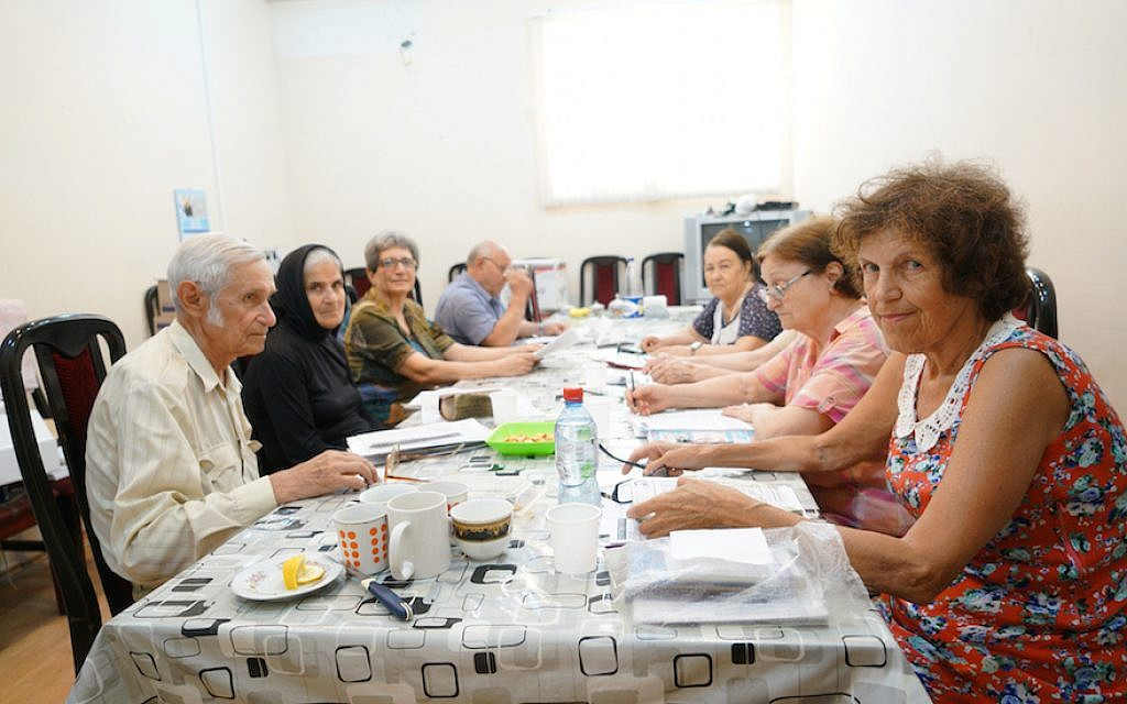 Arnold Zeligman, left, teaching Hebrew to Bella Regimov, wearing head cover, and other students at The Jewish House in Baku, Azerbaijan, July 18, 2018. (Cnaan Liphshiz)
