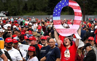 "David Reinert holds up a large ""Q"" sign representing QAnon, a conspiracy group, while waiting in line to see President Donald Trump at a rally in Wilkes-Barre, Pa., on August 2, 2018. (Rick Loomis/Getty Images)"