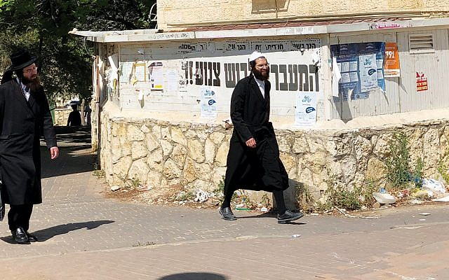 Chasidim walk past a modesty sign in a tension-filled neighborhood. (Photos by Sam Sokol)