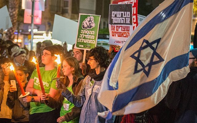 Israeli left-wing activists holding placards and their national flag during a Peace Now march in Tel Aviv, Dec. 19, 2015. (Jack Guez/AFP/Getty Images)