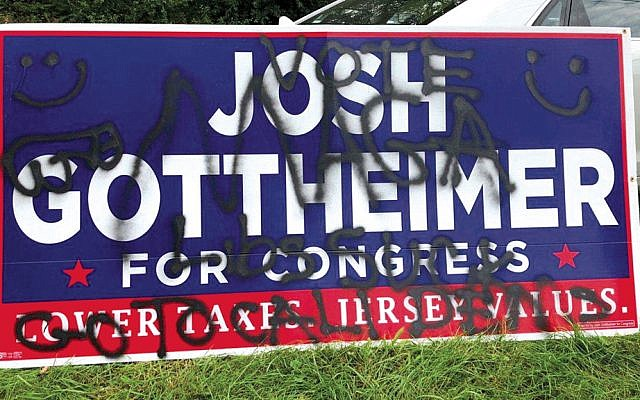 A campaign sign for Representative Josh Gottheimer on the lawn of home in Hampton Township, left, is defaced with anti-Semitic and racist graffiti.