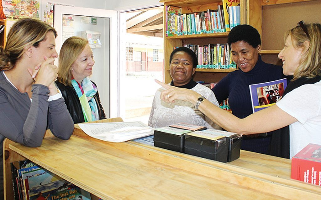 Schechter's Leslie Teicher, Ruth Gafni, and Beryl Bresgi join community librarians in the Langabuya School's first-ever library.