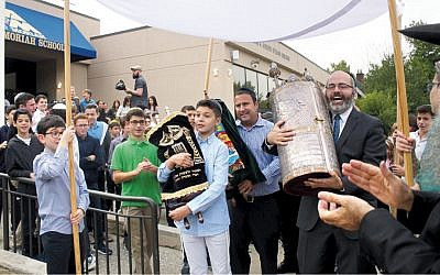 David Bousbib walks the Torah to the street with Moriah board chairman Zvi Rudman and Rabbi Zev Reichman of East Hill Synagogue. (Courtesy Moriah)