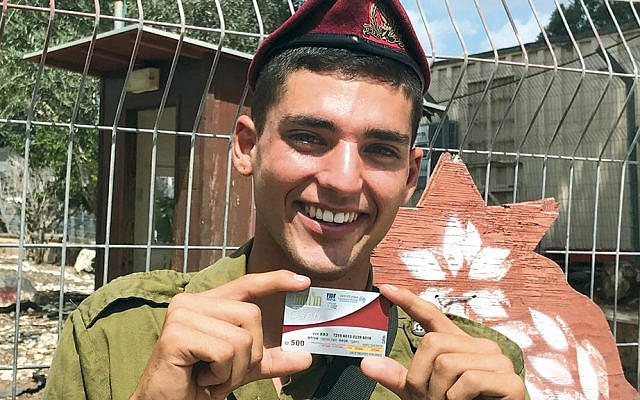 An Israeli soldier receives a Rosh Hashanah Fellowship gift card. (Courtesy of FIDF)