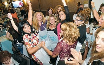 Participants in the Chabad Jewish Center of Suffern's Ann Koenig Mega Challah Bake 6 show their enthusiasm as they prepare to combine the ingredients for more than 1,000 challahs.