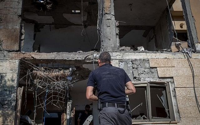 Israeli security forces survey a home hit by a rocket fired from the Gaza Strip in the southern Israeli city of Beersheba on Oct. 17, 2018. (Yonatan Sindel/Flash90)