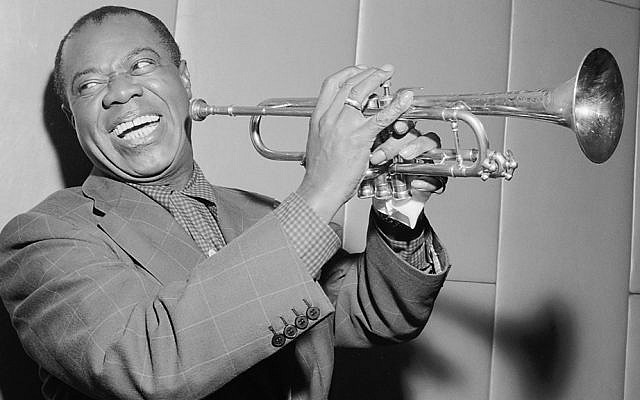 Louis Armstrong flashes his trademark smile in a 1955 photo.