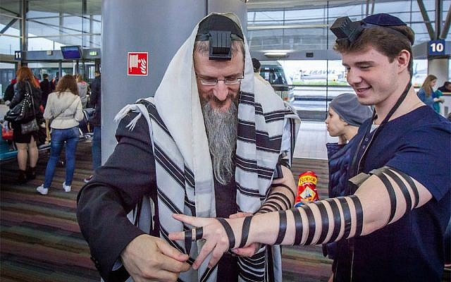 Russia's Chief Rabbi Berel Lazar helps a young man wrap the leather straps of tefillin during a trip to France in 2015. (Courtesy of Yachad)