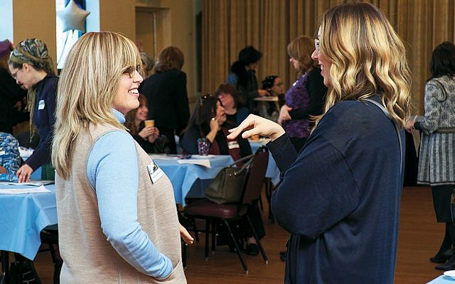 Dr. Adina Shmidman, left, founder of the OU Women's Initiative, listens to an attendee at the professional development day for mikvah attendants.