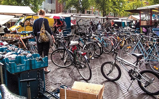 A prospective customer examines the secondhand bicycle area at Amsterdam's Waterloo Square market in 2012. (Ksenia Novikova/Flickr)