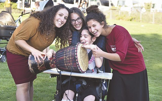 Aleh volunteers help a child learn how to drum at one of the organizations's rehabilitative facilities.