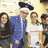 Rabbi Fred Elias poses with Solomon Schechter Day School of Bergen County students as they prepare latkes for the school's annual Chanukah Fry-Off. Students also tested their dreidel-spinning acumen, competing for chocolates, and eating jelly donuts. (Courtesy SSDS)