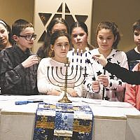 Temple Emeth in Teaneck's religious school students are in Holy Name Medical Center in Teaneck's chapel during Chanukah. They lit the menorah, sang songs, and shared Chanukah cheer. Another celebration was held at the shul during Shabbat services. (Barbara Balkin)