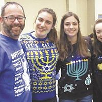 Bergen County High School of Jewish Studies teacher Barnett Goldman, left, with students Julia Holzsager, Brianna Leopold, and Annabelle Simhon, at the BCHSJS Chanukah celebration with sufganiyot, latke-making, chocolate gelt, and ugly Chanukah sweaters. (Courtesy BCHSJS)