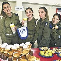 Hundreds of Israel Defense Forces soldiers had Chanukah celebrations at the Ananot Base thanks to Jack and Sheila Usdin, supporters of the New Jersey Friends of the Israel Defense Forces. FIDF's team in Israel brought messages of hope and light — and sufganiyot — to the IDF's Erez Battalion of the Military Police, which the Usdins adopted as part of the FIDF Adopt-A-Battalion Program. (Courtesy of FIDF)