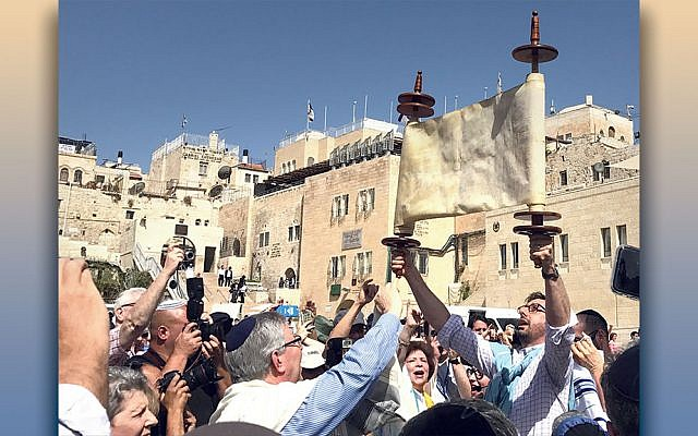 Rabbi Josh Weinberg holds up a Torah scroll at the Kotel as part of the World Union for Progressive Judaism's meeting in Jerusalem in June, 2017. (Rabbi Josh Weinberg)