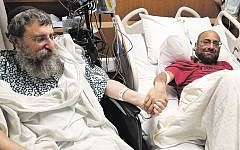 Rabbi Ephraim Simon, left, clasps hands with Adam Levitz at the Cleveland Clinic.