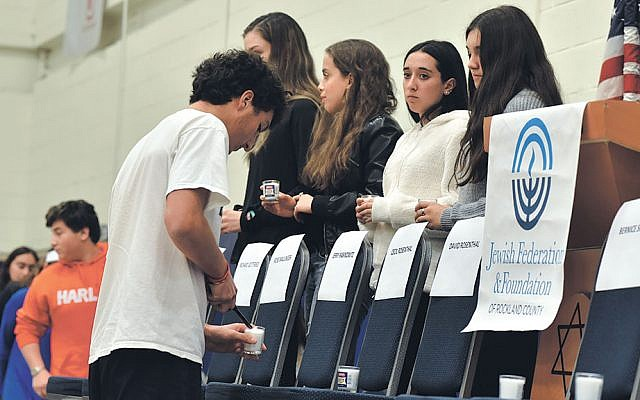 Teenagers stand by empty chairs labeled with the Pittsburgh victims' names.