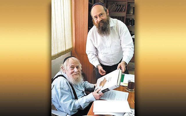 Rabbi Adin Even-Israel Steinsaltz, sitting, and his son, Rabbi Meni Even-Israel, work together at the Steinsaltz Center in June 2018. (Wikimedia Commons)