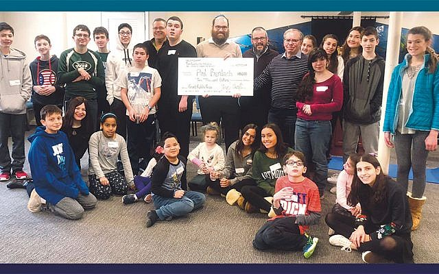 Rabbi Yosef Orenstein, the director of Valley Chabad's Teen Leadership Initiative, holding check, center, with Rabbi Dov Drizin, Valley Chabad's executive director, to his right, at a Friendship Circle program. (Courtesy Valley Chabad)