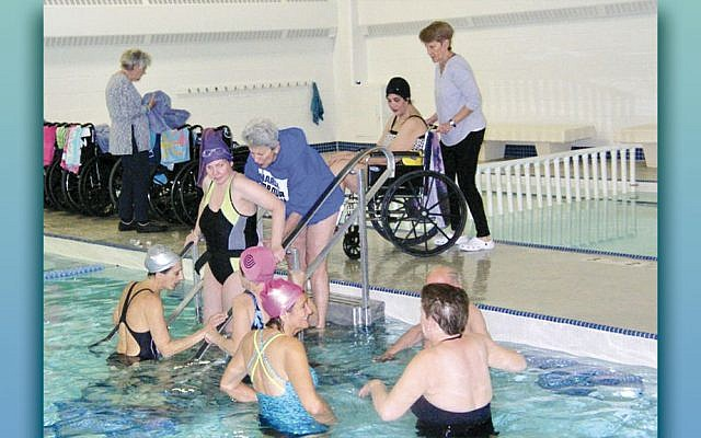 """NCJW volunteers work with swimmers at """"Swim-In,"""" a unique aquatherapy program for people with multiple sclerosis. More volunteers are needed to help the swimmers both in and out of the pool. (NCJW)"""
