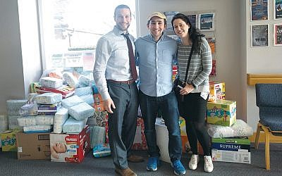 From left, Rabbi Ely Shestack of Ahavat Achim and Andrew and Kira Wigod  stand in front of a stack of donated diapers.
