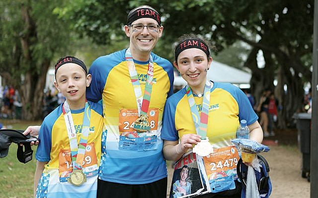 """Eli Gottesfeld's z""""l, brother, Shalom Meir, left, Dr. Andrew Silverman, and Eli's sister, Yehudis, are pictured together. Shalom Meir joined the doctor, and his sister at race end before the finish line. (Benji Weintraub for Chai Lifeline)"""