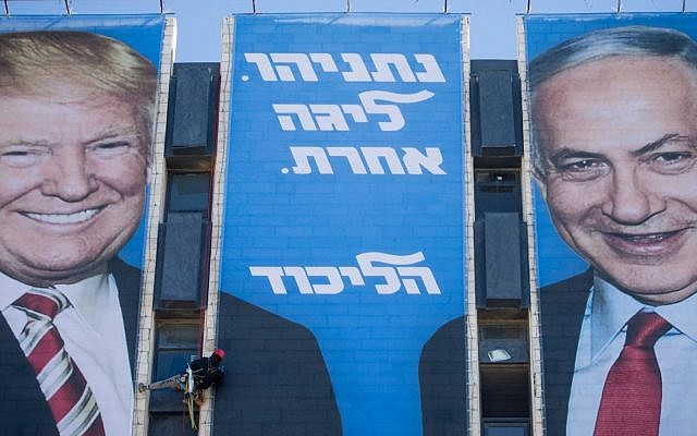 An Israeli worker hangs a campaign billboard of President Donald Trump shaking hands with Prime Minister Benjamin Netanyahu on a Jerusalem building on Feb. 3, 2019. (Yonatan Sindel/Flash90)