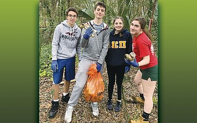 Alan Rosenberg, left, Tyler Leopold, Brianna Leopold, and Julia Holzsager help clean a park as part of tikkun olam activities. (Courtesy BCHSJS)