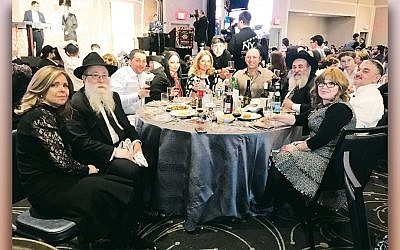 Kreina and program director Rabbi Baruch Lepkivker are surrounded by guests; Bris Avrohom's executive director, Rabbi Mordechai Kanelsky, is third from right.  (Courtesy Bris Avrohom)