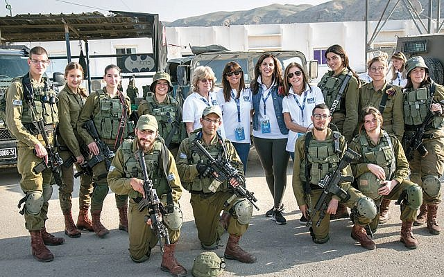 """Taran Chernin of Woodcliff Lake, second from right, wearing a white shirt, stands with other mission participants from the tristate region and the IDF """"Lions of the Valley"""" 47th Battalion, an infantry battalion composed of female and male combat soldiers. (Nir Kafri)"""