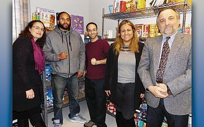 Maria Salerno and Raymond Garcia, both of CCAN, left, with Michael Dworkis and Valery Vertiz of JFCS, and Peter Ruccione, CCAN, at the JFCS Food Pantry in Teaneck. (Courtesy JFCS)