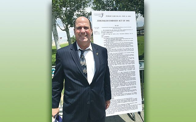 Farley Weiss, president of the National Council of Young Israel, stands next to the text of the Jerusalem Embassy Act of 1995. (Farley Weiss)