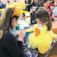 The JCC of Paramus/Congregation Beth Tikvah, Congregation Beth Tefillah, and the Sephardic Congregation of Paramus held a joint Purim carnival on March 17 at the JCC/CBT. Here, Talya Safier, president of Beth Tefillah paints a design on a young carnival-goer. (Sandy Alpern)