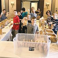 Sixth graders pack hamantaschen for distribution as part of the efforts by the sisterhood of Temple Sinai in Tenafly to distribute 700 mishloach manot bags for congregants, early childhood school families, and synagogue staff, and to donate and deliver 50 bags for Meals on Wheels to clients at Jewish Family & Children's Services of Northern New Jersey. On March 17, more than 50 volunteers packed insulated lunch bags with kosher food, and hamentaschen, and more than 50 volunteers delivered them. (Courtesy Temple Sinai)