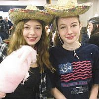 Hayley Leopold and Ilana Unger, students at the Bergen County High School of Jewish Studies, dressed up for a pre-Purim celebration last Sunday. After shortened classes, students decorated Purim masks while parents and teachers helped make and distribute popcorn and cotton candy. (Courtesy BCHSJS)