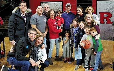 Noga Pelc, back row second from right in Rutgers sweatshirt, her mom, far right, and her cousin Rose Konigsberg, center, holding her grandson, are pictured at a recent Rutgers University game with family, and friends. (Photo provided)
